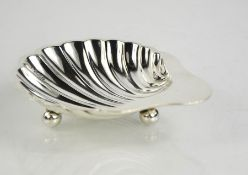 A sterling silver scallop design butter dish, with three ball feet to the bottom, Sheffield 1923,
