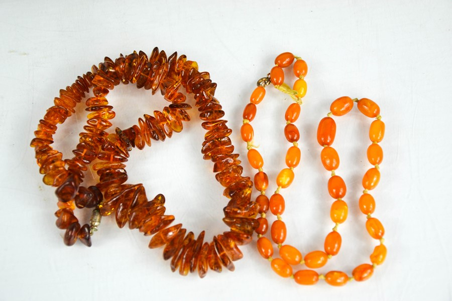 Two amber necklaces, one raw cut clear amber beaded necklace, 43.5g, and an oval cloudy amber