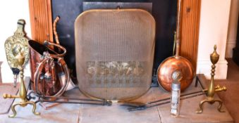 A quantity of antique copper and brass ware to include warming pan, coal scuttle, andirons and