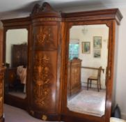 An impressive Edwardian mahogany marquetry inlaid triple wardrobe, the bow front central cupboard