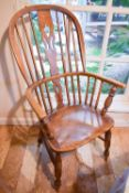 A 19th century elm Windsor armchair, with hoop back and bowed arm rail pierced with spindles, the