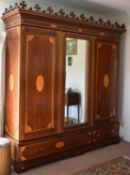 A large 19th century mahogany marquetry inlaid wardrobe with central mirror flanked by two doors