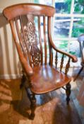 A large 19th century oak kitchen chair, with decoratively carved and pierced splat, the arms