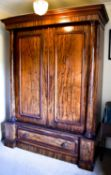 A Victorian mahogany wardrobe with two cupboard doors flanked by columns and raised on a base with