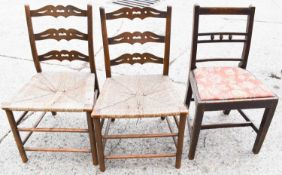 Two early 19th century ladder back chairs with rush seats together with an Edwardian upholstered