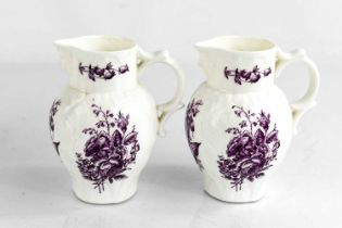 A Royal Worcester pair of small jugs, modelled with face masks, painted with purple floral sprays,