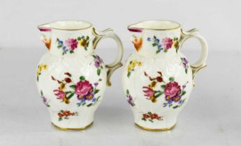 A pair of Royal Worcester leaf moulded jugs with painted roses, face mask spouts and scroll handles,