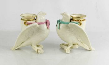 A pair of Royal Worcester porcelain spill vases, modelled as doves perched on a branch with urn to