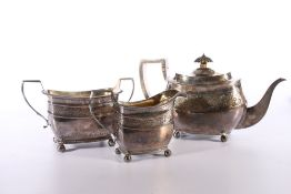 George III silver three piece tea set of boat shape with engraved band of foliage designs by maker