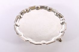 George V silver salver with piecrust edge raised on three scroll feet by Mappin and Webb Sheffield