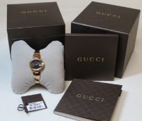 "Gucci lady's stainless steel wristwatch with black dial, oval ""G"" bezel, on tapered bangle with"
