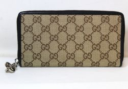 Gucci zip around wallet in GG canvas with brown leather trim and white metal zip pull.
