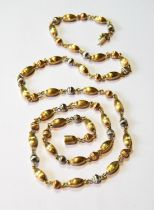 18ct coloured gold opera length necklace of textured oval and spherical beads, 31g.