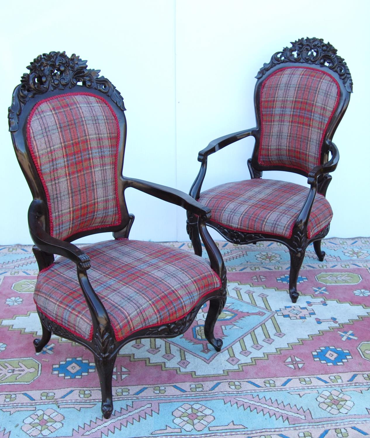 Pair of Victorian-style open armchairs with cushioned backs mounted by floral carved panels,