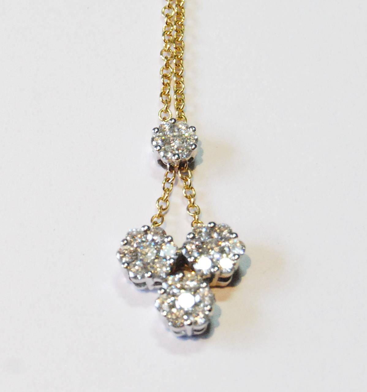 Diamond pendant with three clusters of seven brilliants dependent from another, smaller, in yellow
