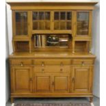 Oak Art Nouveau style dining room suite comprising a dresser, the upper section enclosed by glazed