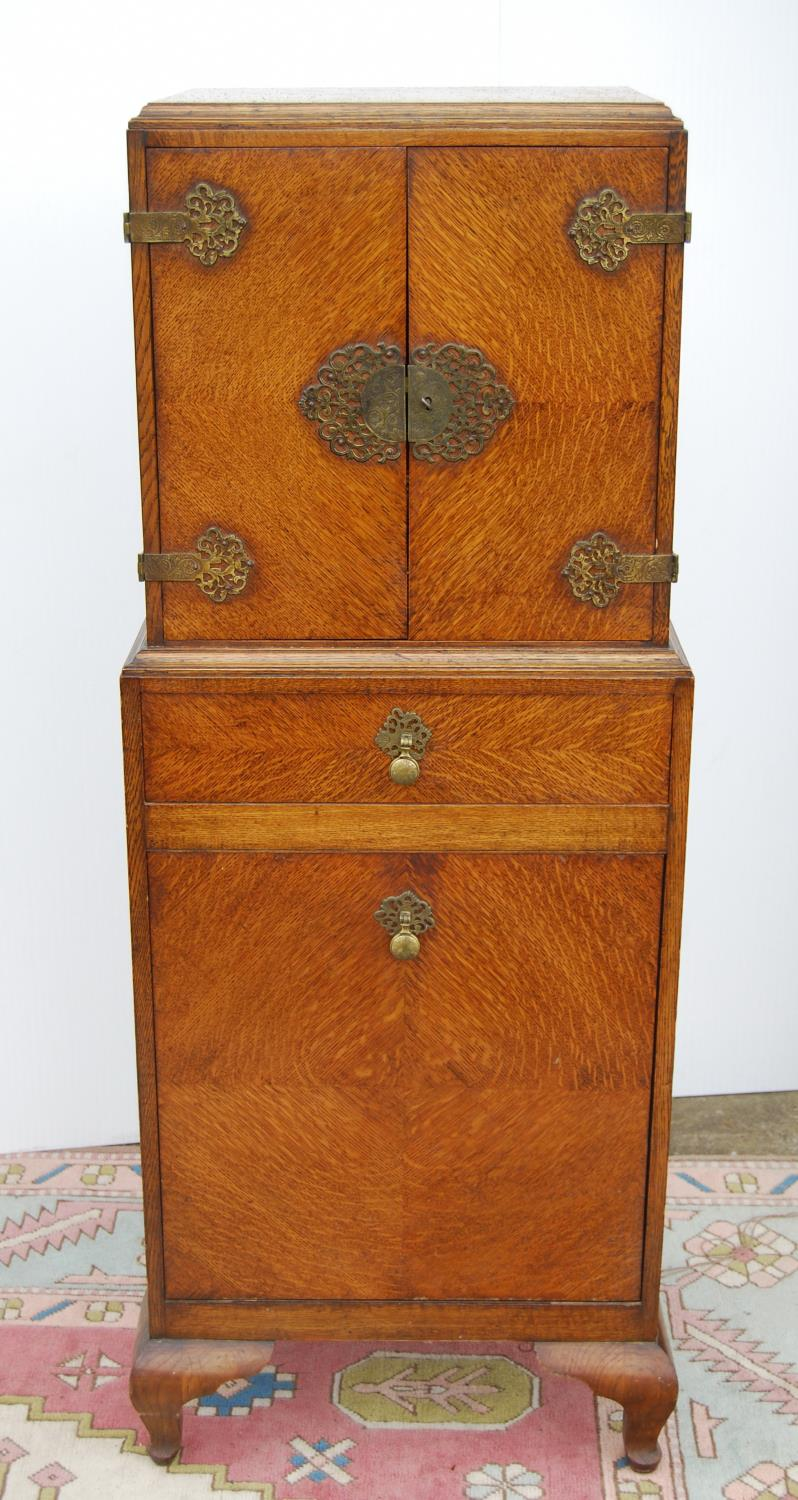 Edwardian oak cabinet on stand, the rectangular top above a cupboard with elaborate hinges and