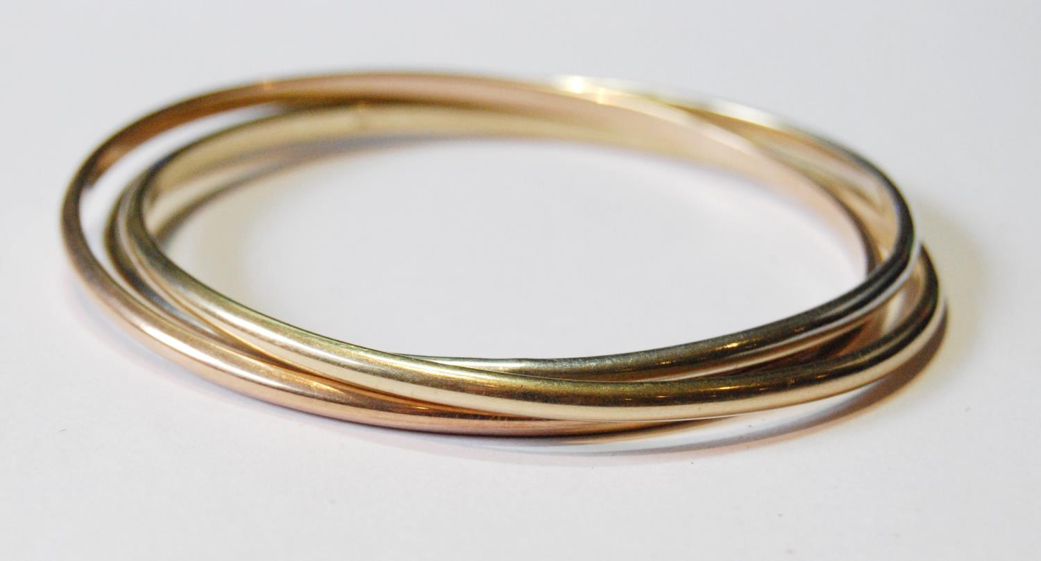 Three coloured 9ct gold slave bangles of Russian style, 37g.
