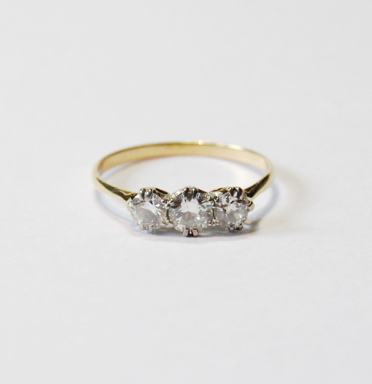 Diamond three-stone ring, the largest brilliant approximately .5ct, in gold, size P.
