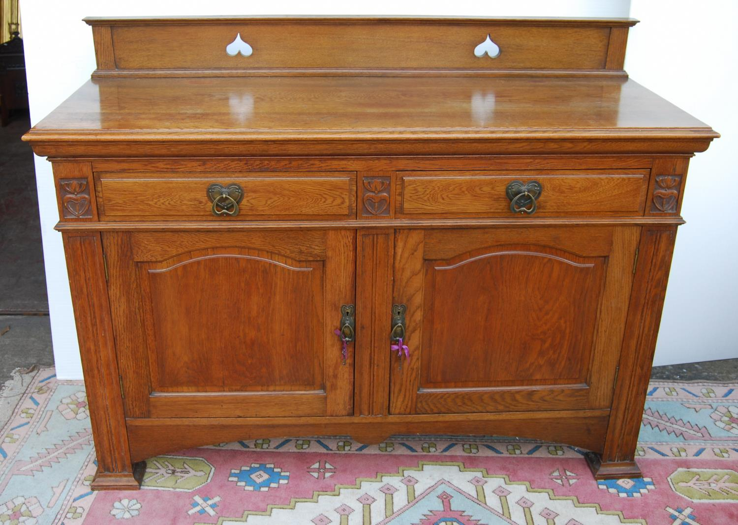 Aesthetic oak sideboard, the back panel with pierced inverted hearts, moulded rectangular top over