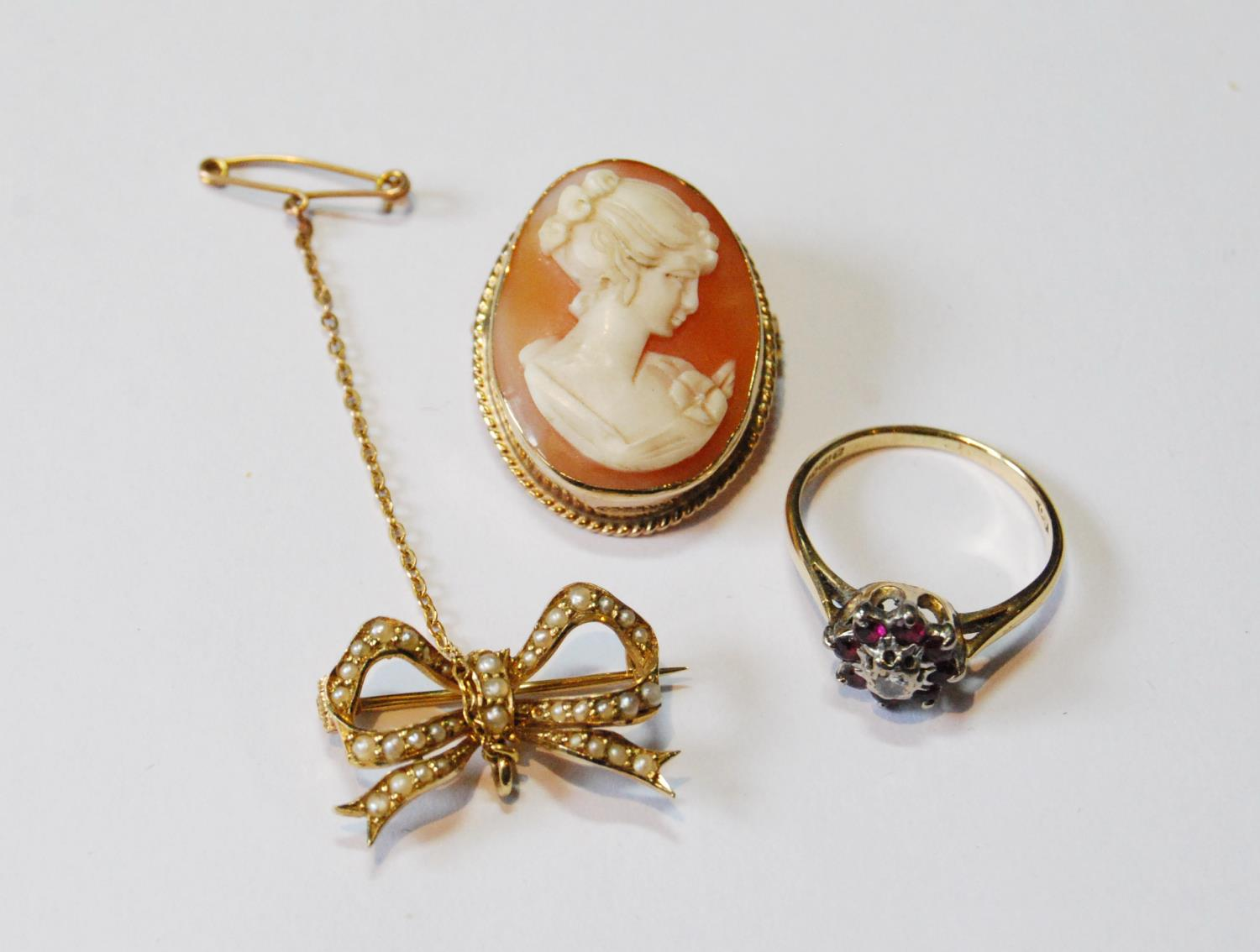 Ruby and diamond ring in 18ct gold, a cameo brooch and a pearl bow brooch.