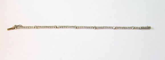 Diamond line bracelet with seven millegrain-set and sixty-three smaller brilliants, in white gold.