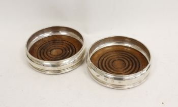 Pair of silver decanter stands with beech bases. 1973