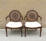 A pair of Sheraton revival mahogany open elbow chairs, the bergere caned circular backs with central