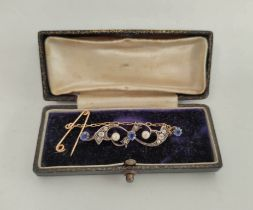 Edwardian gold brooch with scrolls of three sapphires and diamonds in gold and silver.
