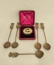 Five Indonesian silver coffee spoons and a delicately carved ivory brooch depicting a deer.
