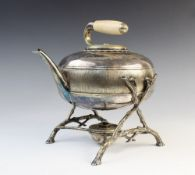 A novelty white metal spirit kettle in the form of a curling stone, with ivory handle to bayonet