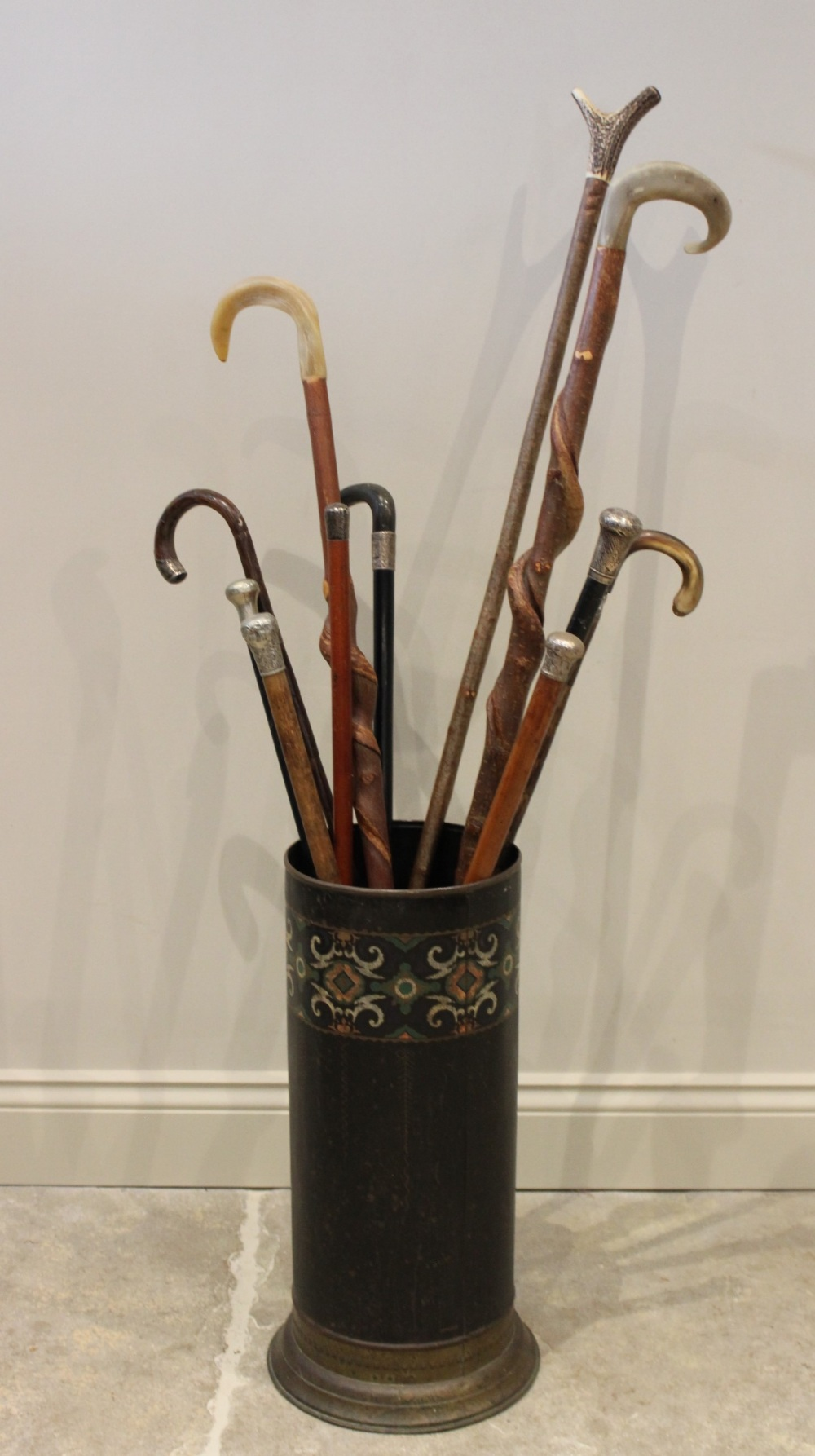 A stick stand, containing assorted walking sticks, to include six silver mounted examples, and