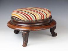 A Victorian mahogany circular foot stool, in striped fabric, raised upon three squat cabriole legs