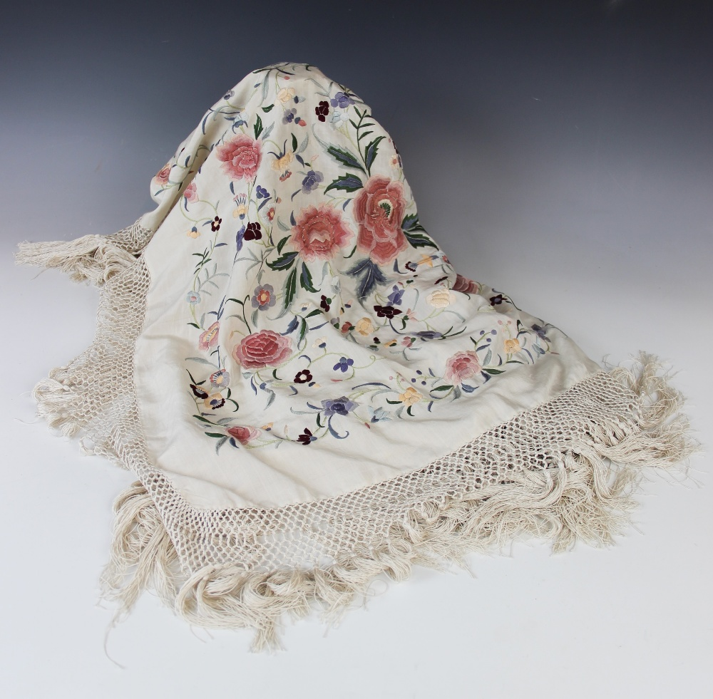 A Chinese polychrome florally decorated machine embroidered silk piano shawl, against a cream