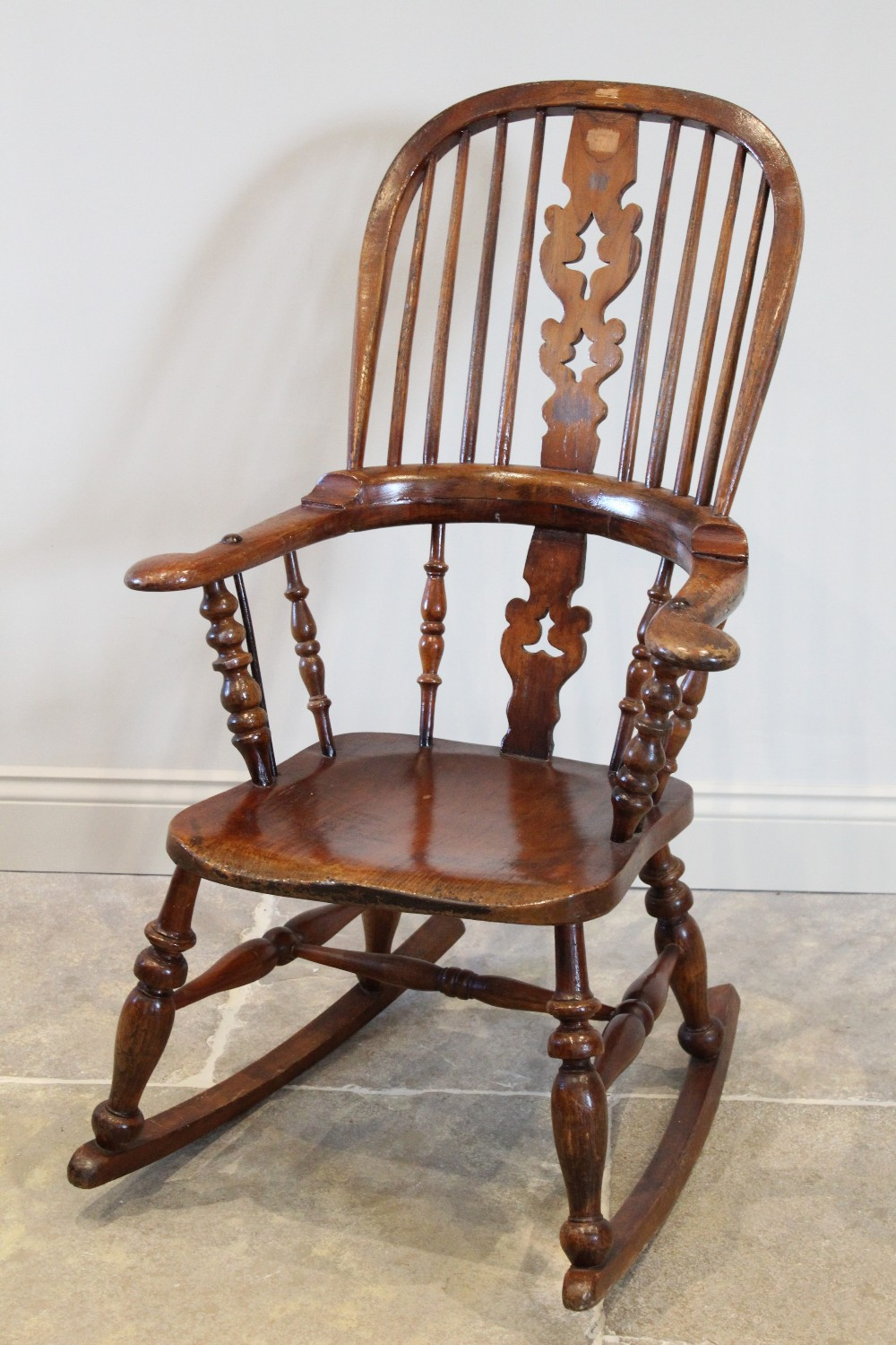 A Victorian and later stained elm and ash Windsor farmhouse rocking chair, the hoop back with
