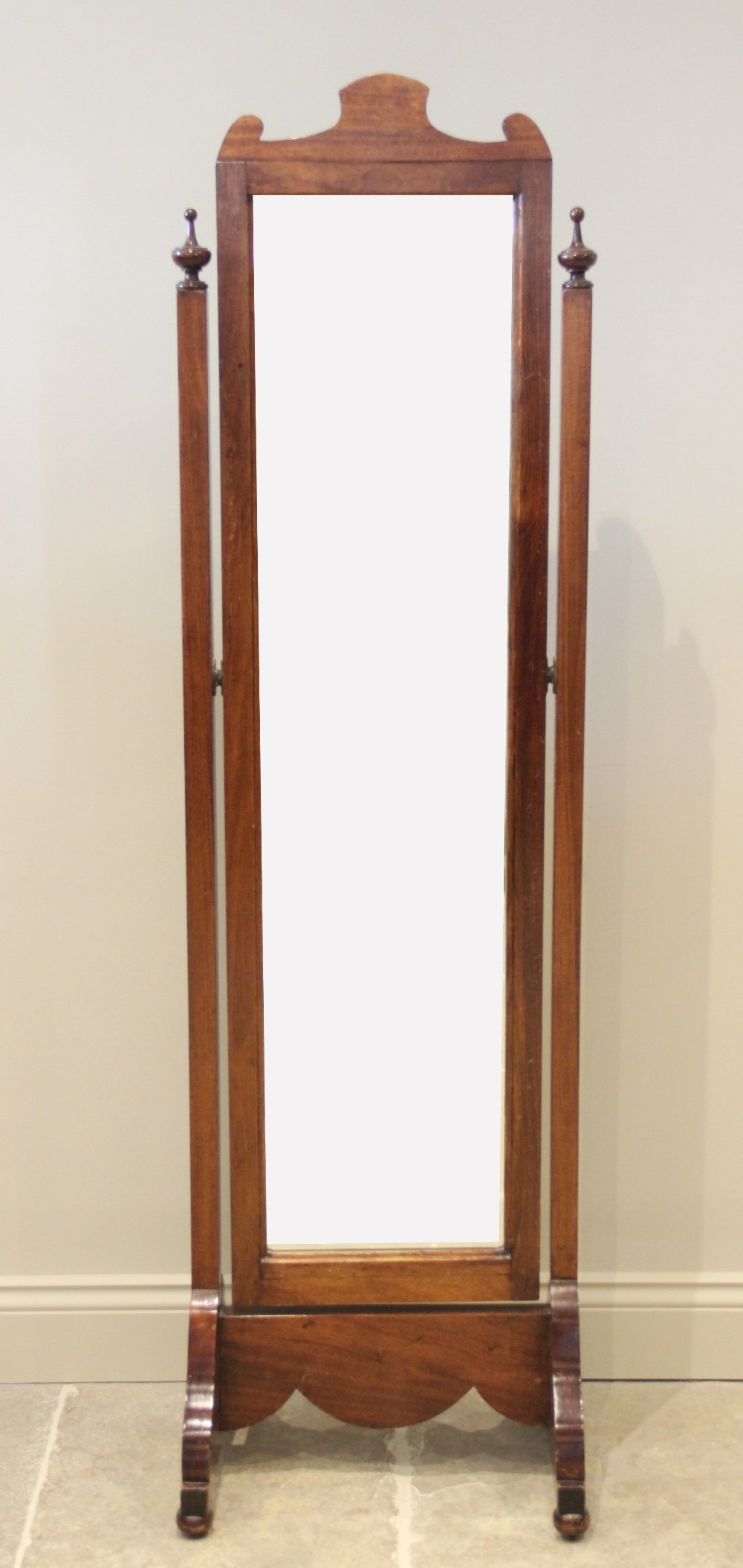 An early 20th century walnut framed cheval mirror, the rectangular bevelled plate raised upon