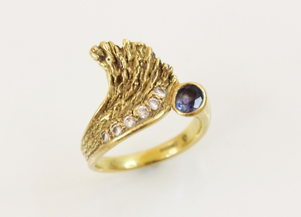 A sapphire and diamond 18ct gold ring, designed as an open wing, set with an oval mixed cut sapphire