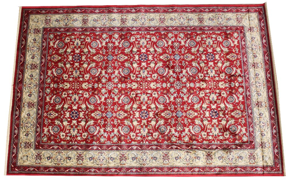 A full pile rich red ground Kashmir all-over floral pattern design surrounded by a gold border,