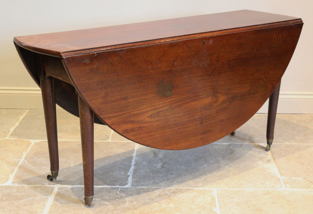 A George III oval drop leaf table, the mahogany top raised upon associated oak legs of tapering