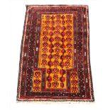 A hand woven full pile Afghan Baluchi Nomadic prayer rug, with an orange ground, 128cm x 81cm