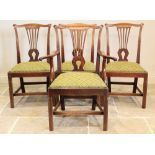 A set of seven George III mahogany Hepplewhite style dining chairs, each chair with a pierced