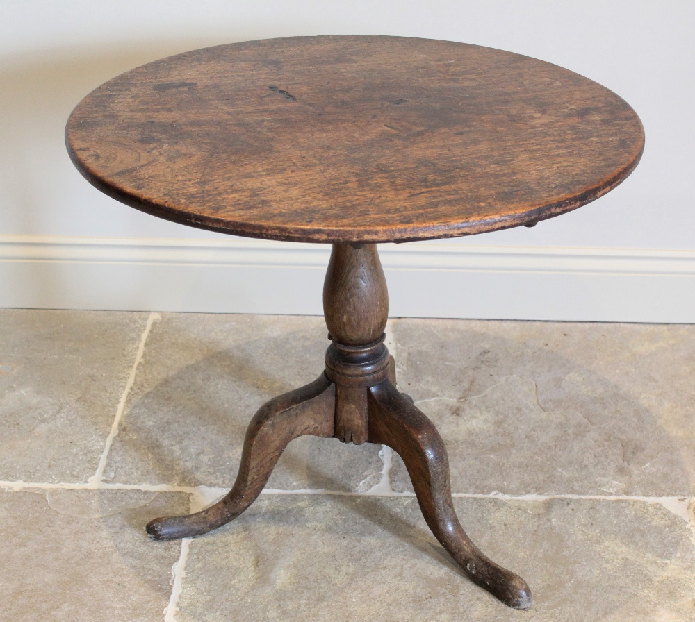 A George III oak tripod table, the circular top raised upon a baluster column extending to three