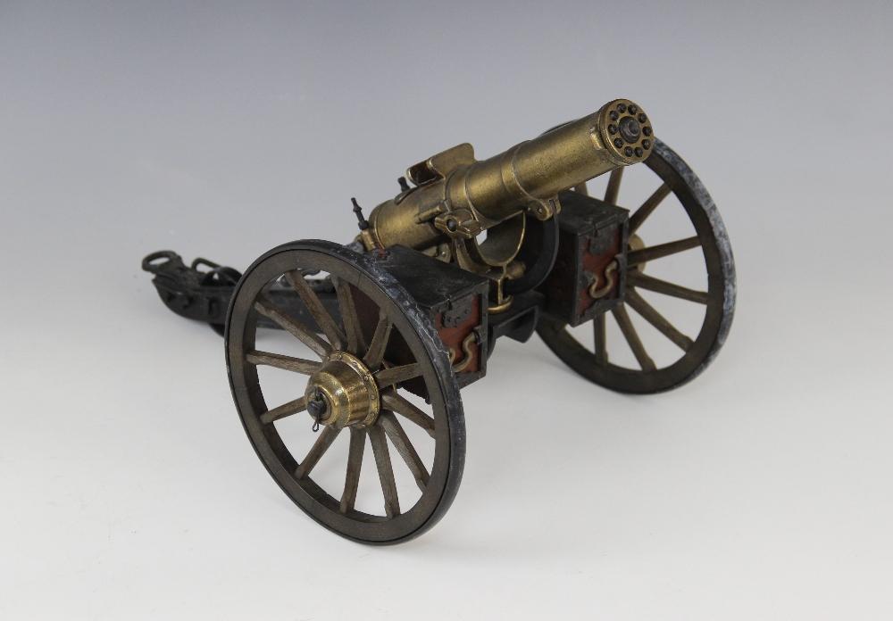 A desktop model of a Gatling field gun, the turned brass barrel set to a tilt mechanism on painted