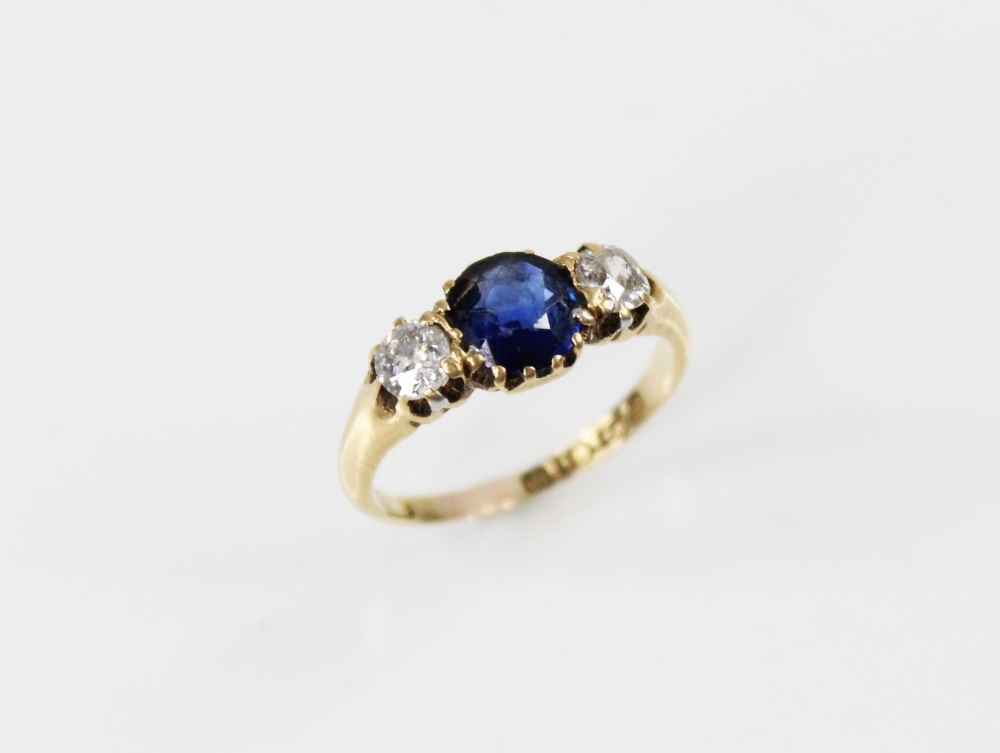 An Edwardian sapphire and diamond three stone ring, comprising a round mixed cut sapphire