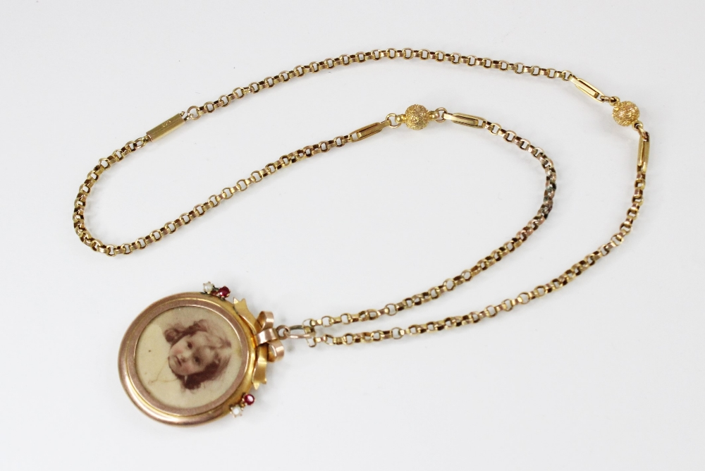 An Edwardian 9ct gold picture pendant, of circular form surmounted by a bow, set with small rubies