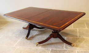 A Regency style twin pillar mahogany dining table, late 20th century, the rectangular satinwood