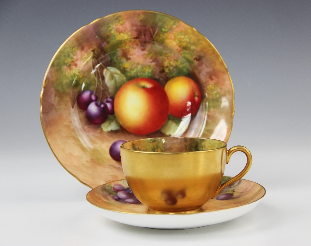 A Royal Worcester porcelain trio, mid 20th century, comprising a teacup, the interior hand painted
