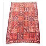 A red ground vintage Bakhtiari region carpet, the central panel with twenty eight alternating