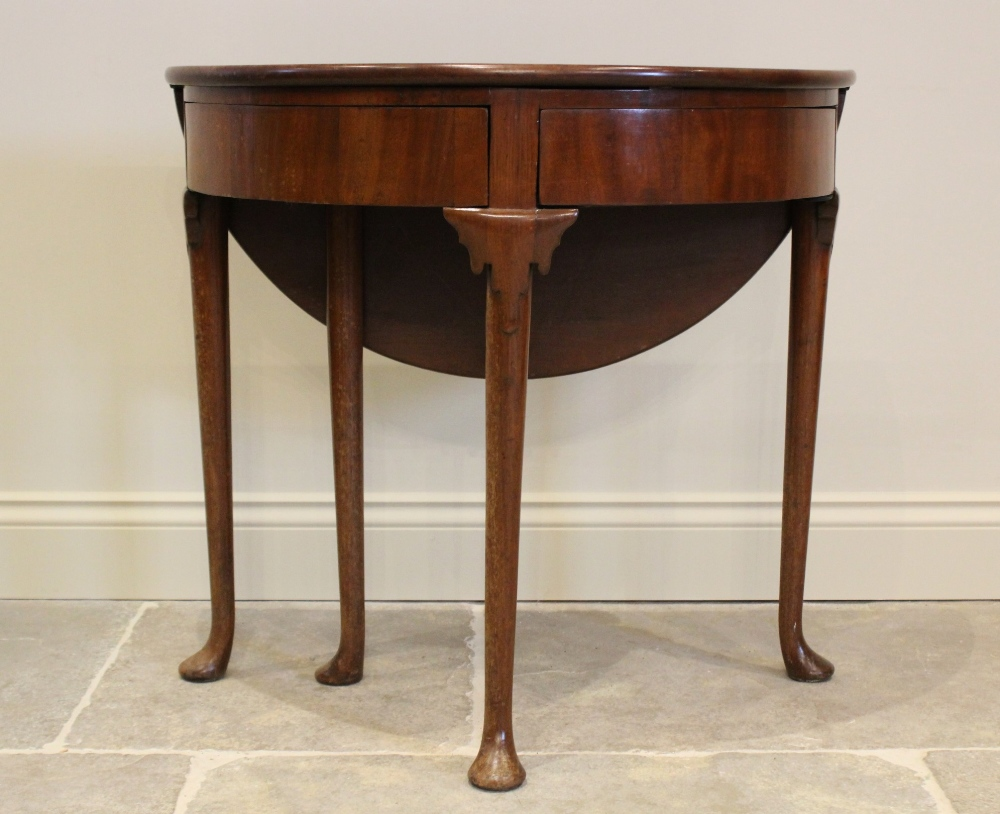 A mid 18th century mahogany folding tea table, the demi-lune folding top above two hinged drawers,