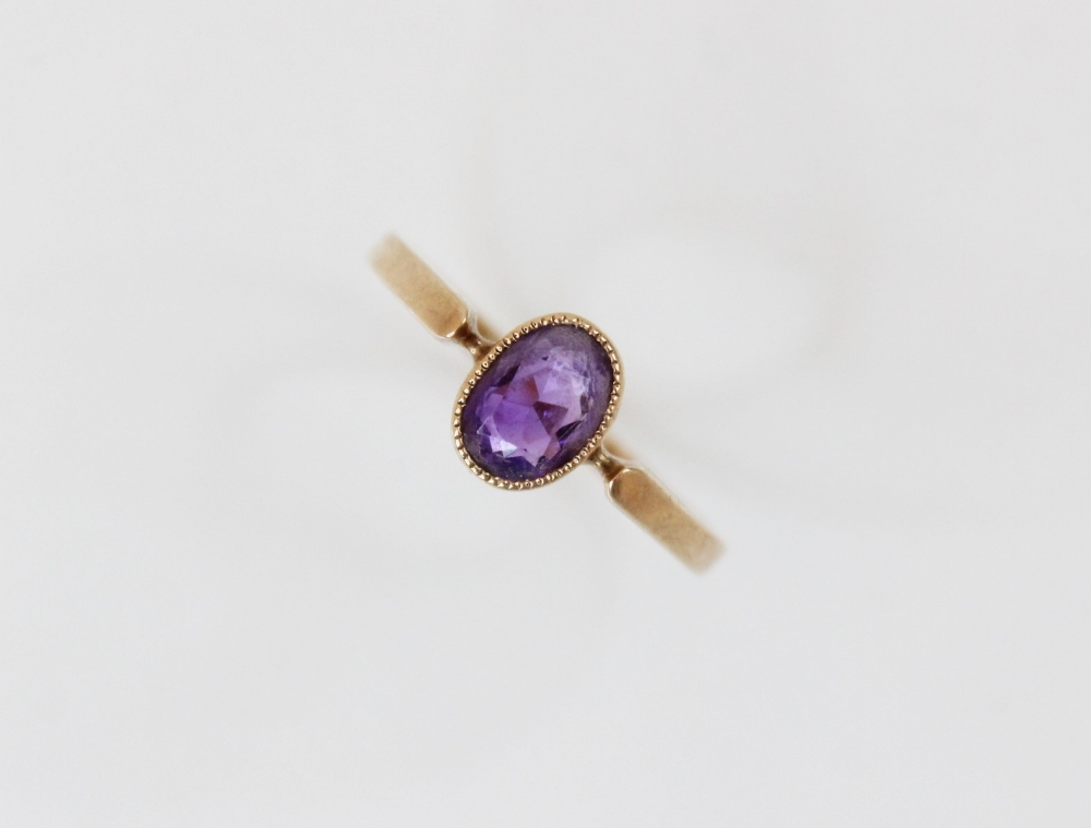 A late Edwardian amethyst set 9ct gold ring, the central oval mixed cut amethyst (measuring 6.5mm